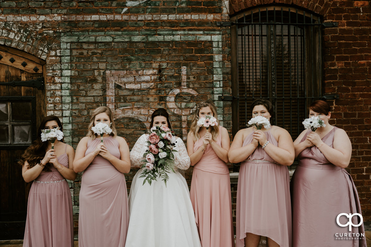Bridesmaids holding flowers over their faces.