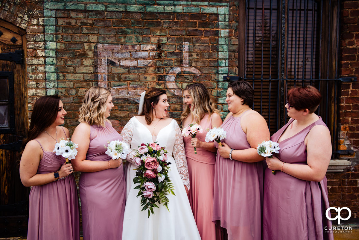 Bride and her bridesmaids having fun before the wedding ceremony.