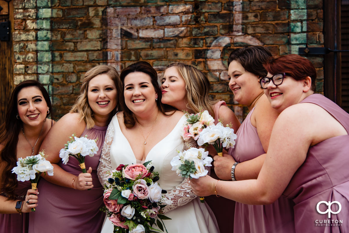 Bridesmaids hugging the bride before she walks down the aisle.