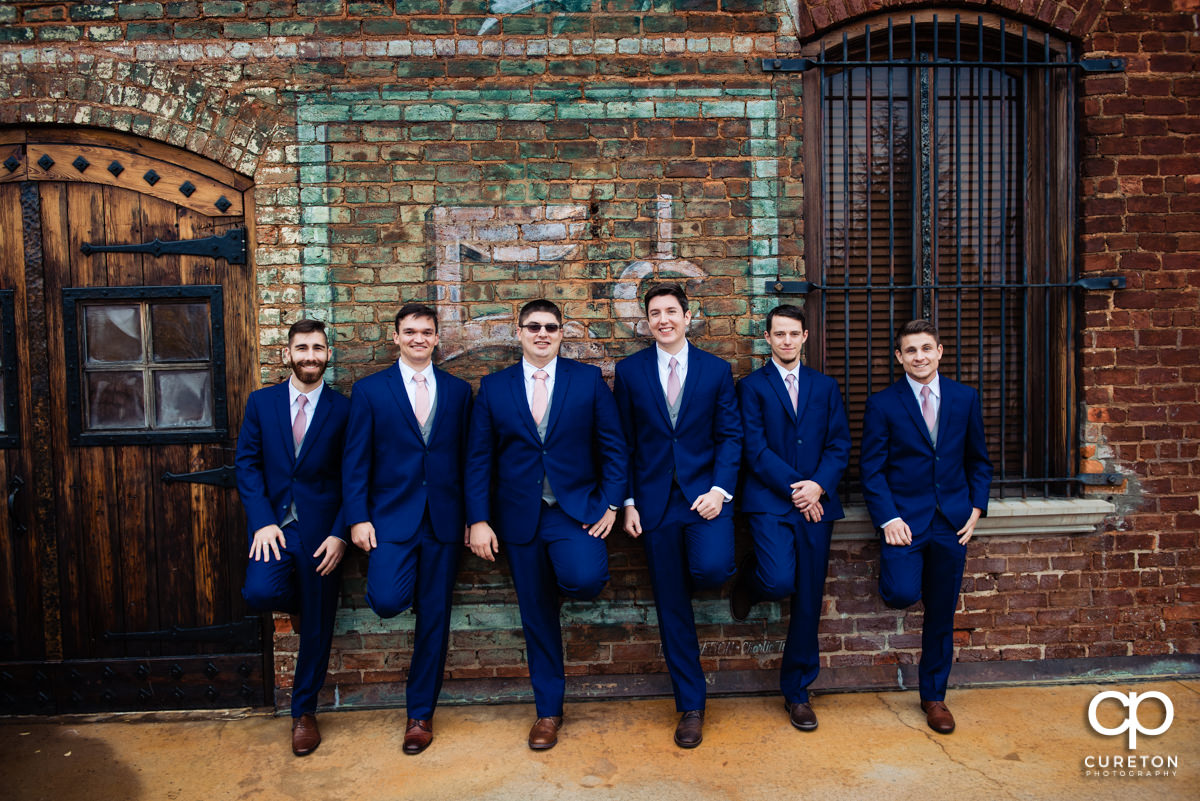 Groom and groomsmen leaning up against an antique brick wall.