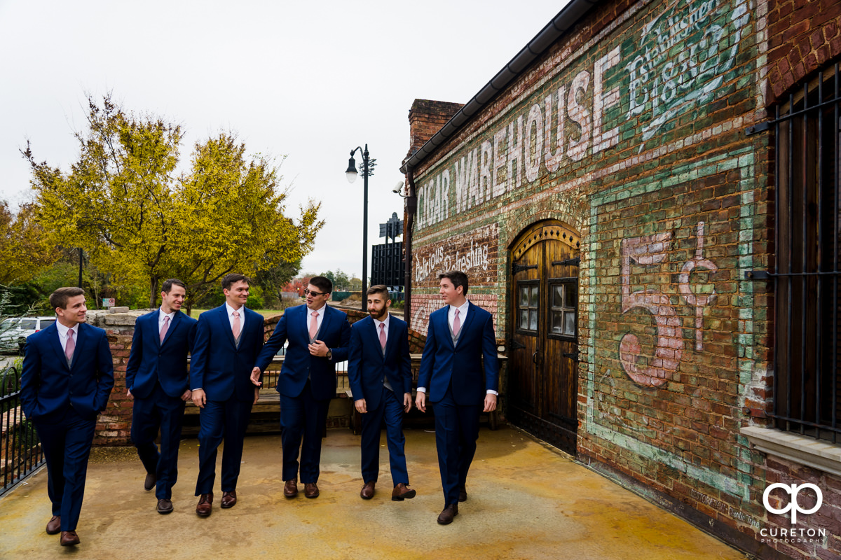Groom and groomsmen walking on the deck at Old Cigar Warehouse.