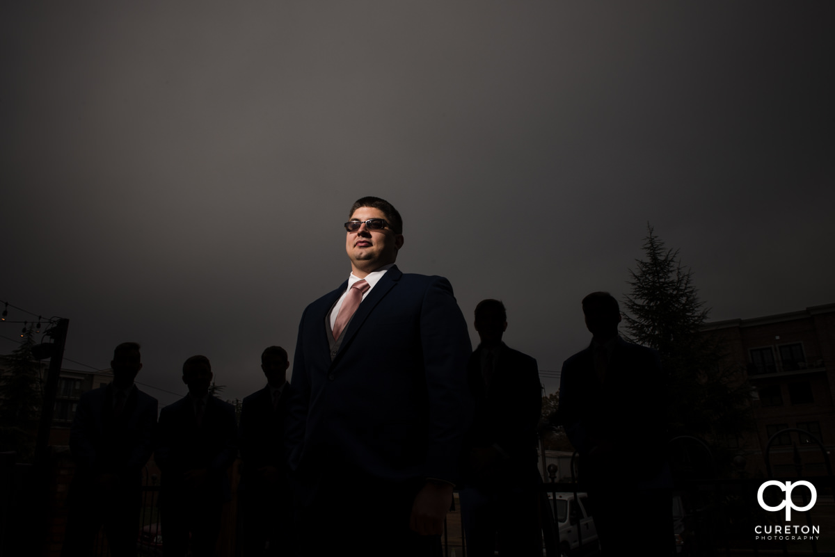 Groom in front of his silhouetted groomsmen.