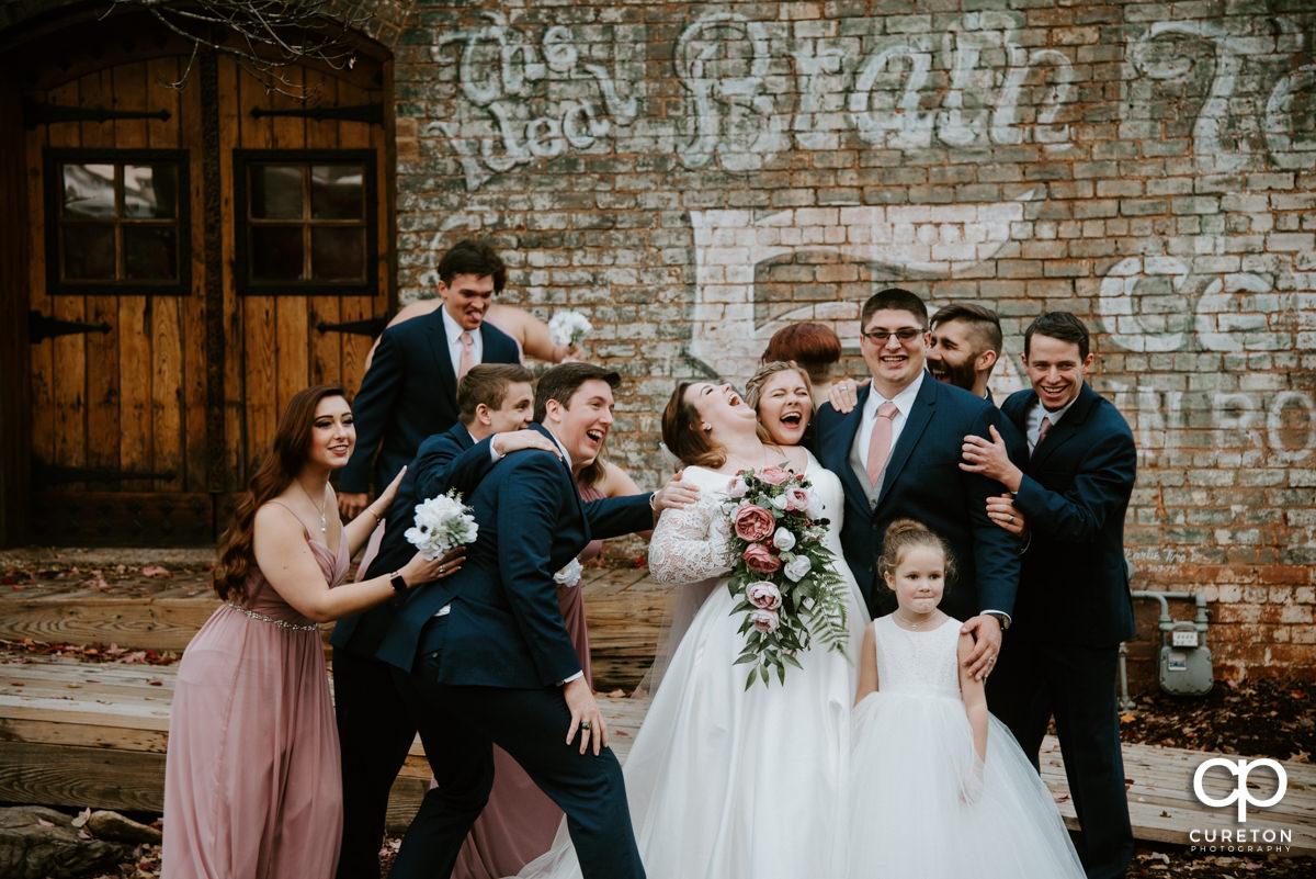 Wedding party hugging the bride.