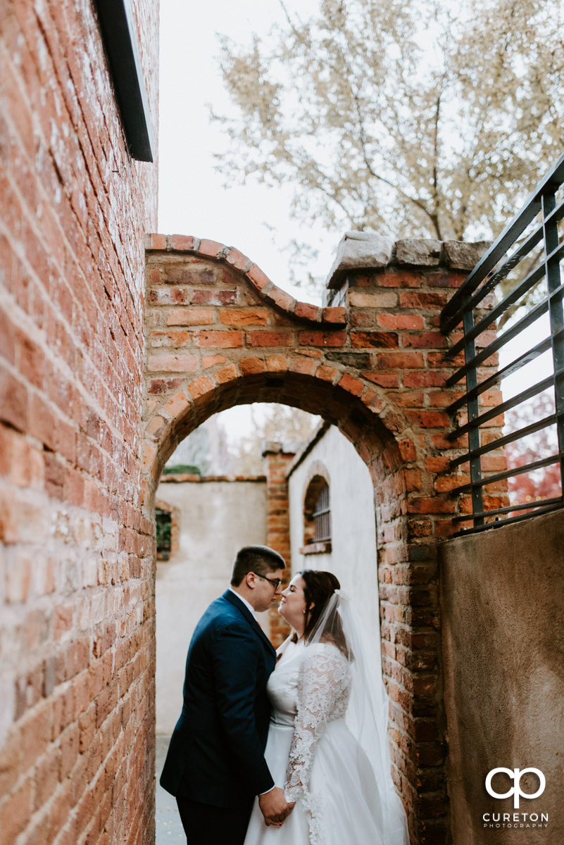 Bride and groom standing underneath an archway.