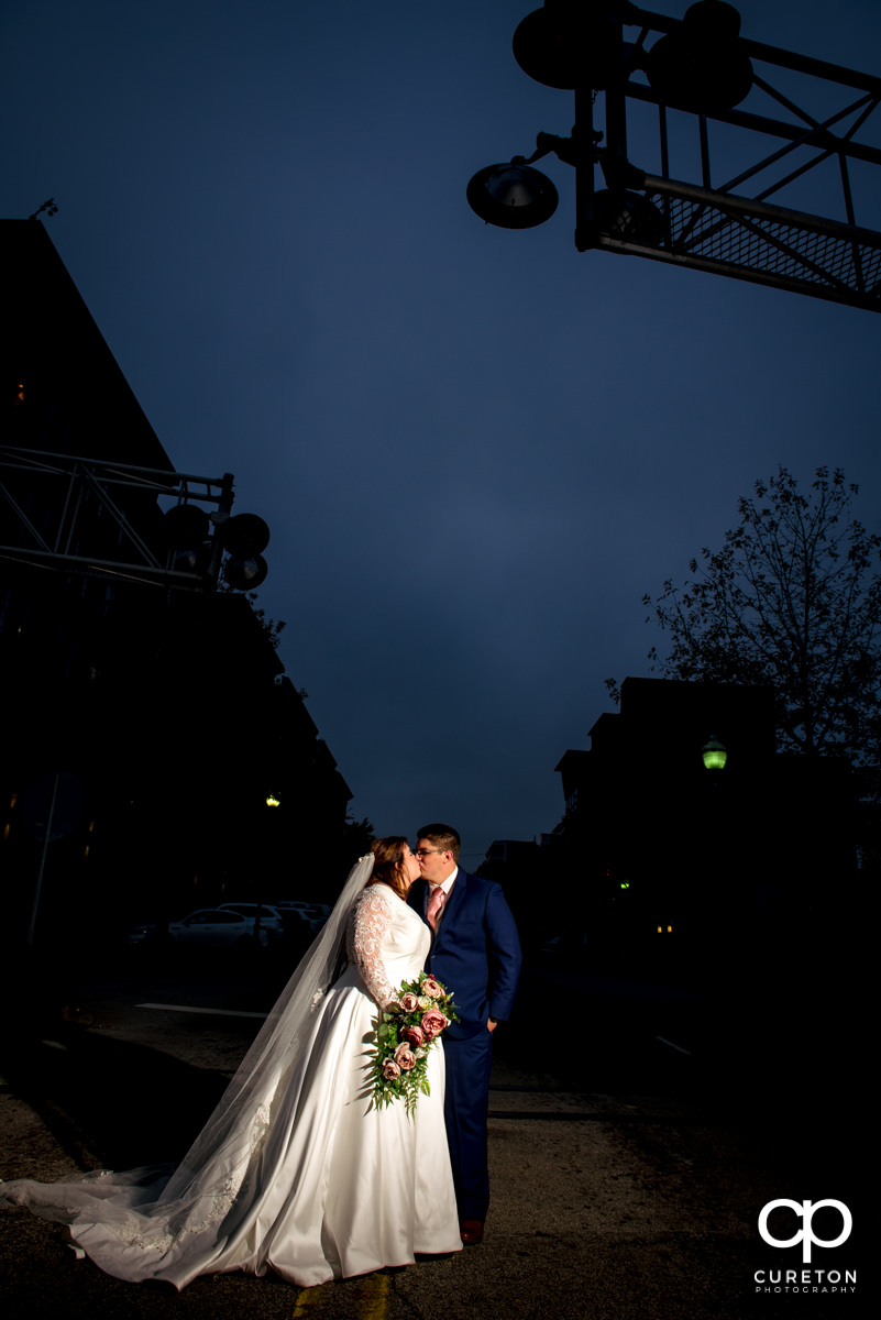 Bride and groom kissing on Main Street in downtown Greenville,SC.