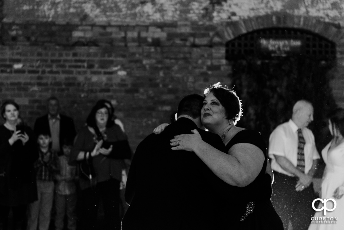 Groom's mom hugging him at the wedding reception.