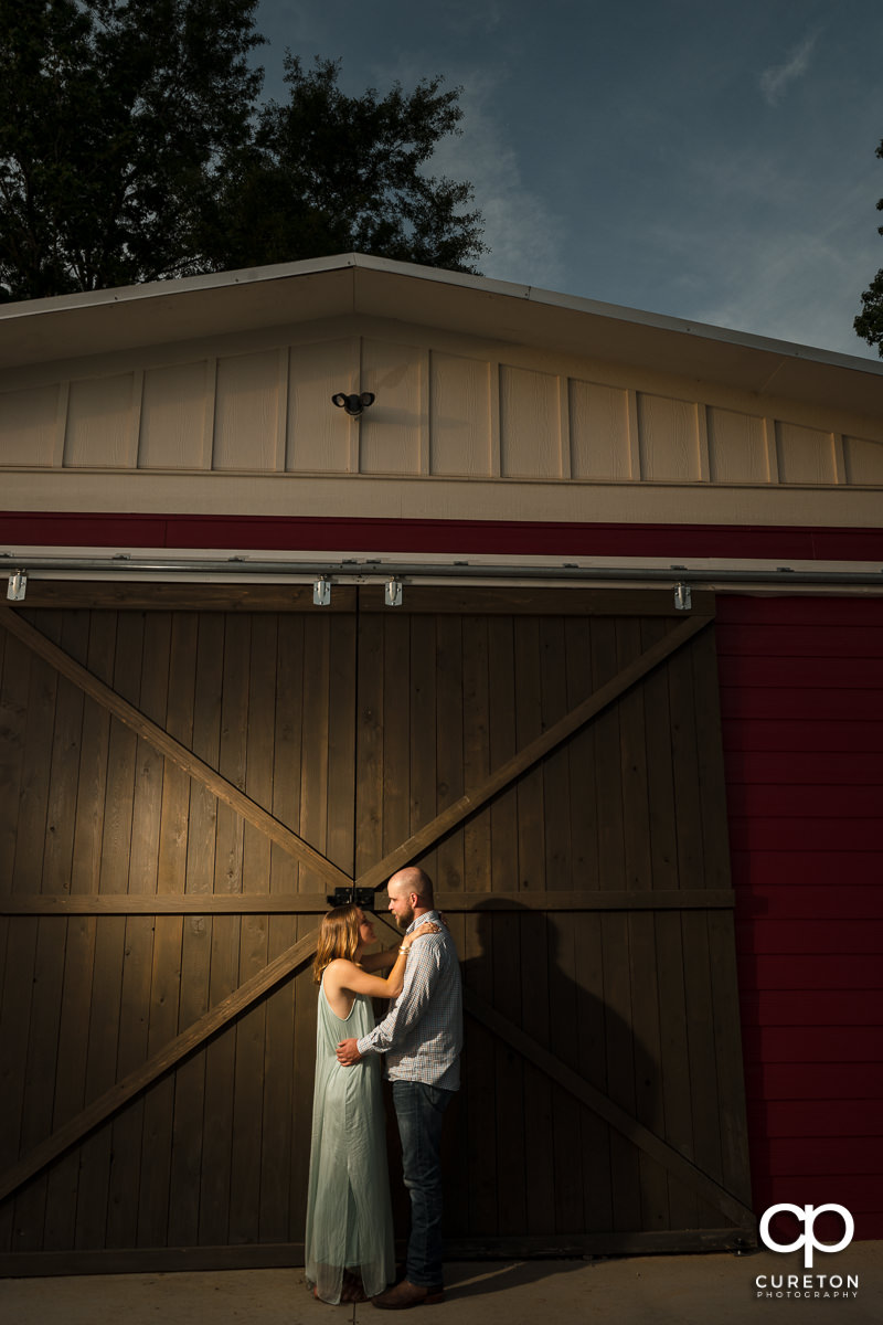 Future bride and groom dancing in front of a barn.