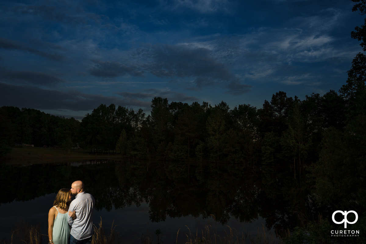 Man kissing his fiancee on the forehead in front of a pond at sunset during a family farm engagement session in Gray Court,SC.