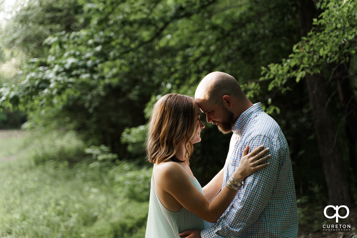 Future bride and groom snuggling in the woods during a family farm engagement session in Gray Court,SC.