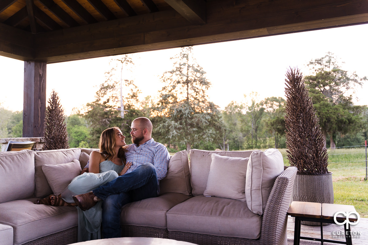 Man relaxing in an outdoor pavilion with his fiancee during a family farm engagement session in Gray Court,SC.
