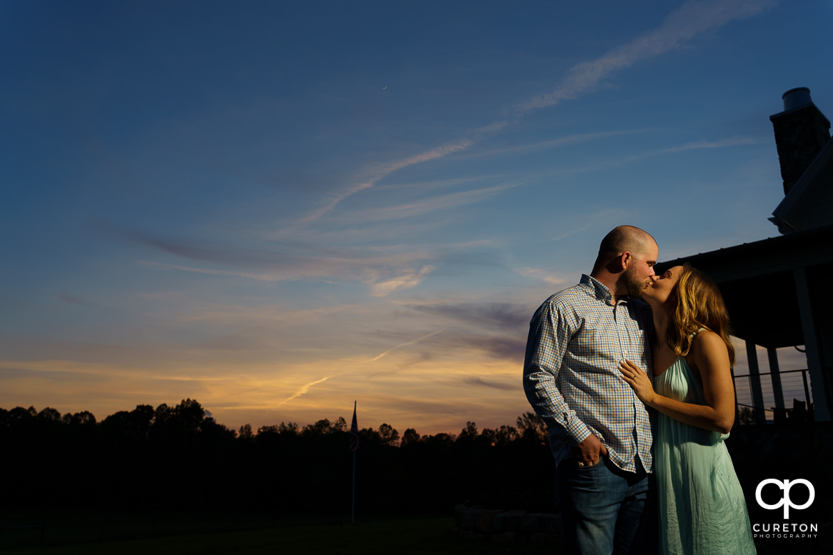Man kissing his fiancee at sunset.