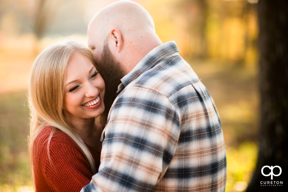 Man whispering into his fiancee's ear during a fall engagement session at Famoda Farm in Greenville,SC.