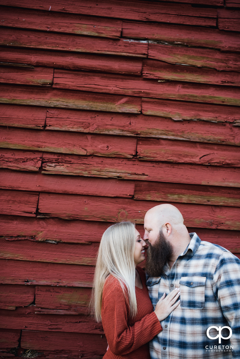 Couple eskimo kissing in front of a red barn at Famoda Farm.