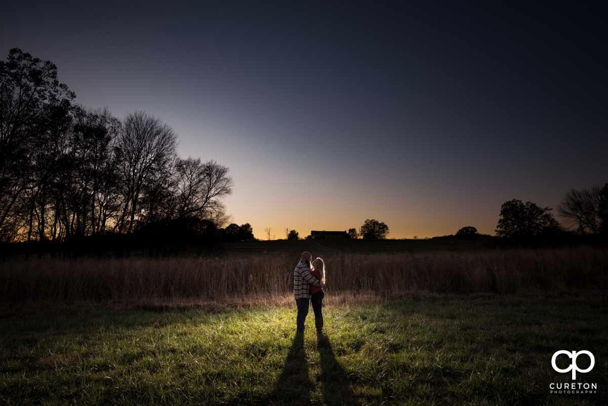 Man and his future bride dancing in a field at sunset during a fall engagement session at Famoda Farm near Greenville,SC.