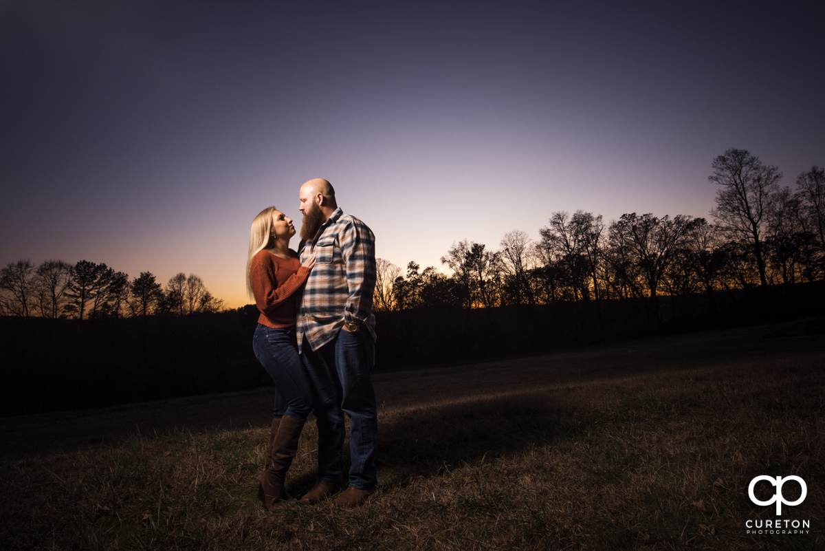 Future bride and groom hugging at sunset at Famoda Farm during their engagement session.