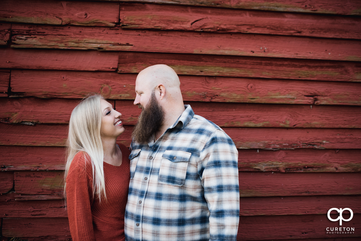 Engaged couple in front of a red barn.