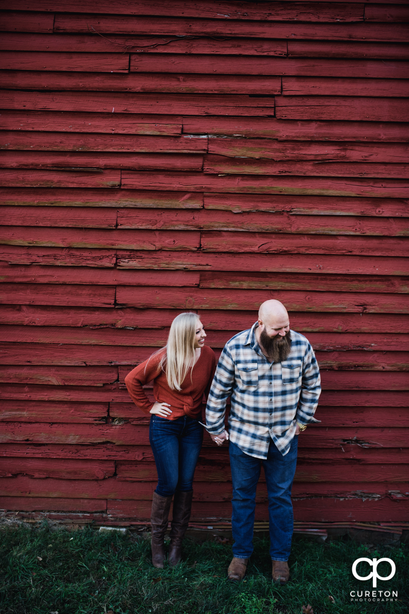 Engaged couple laughing in front of an old red barn at Famoda Farm.