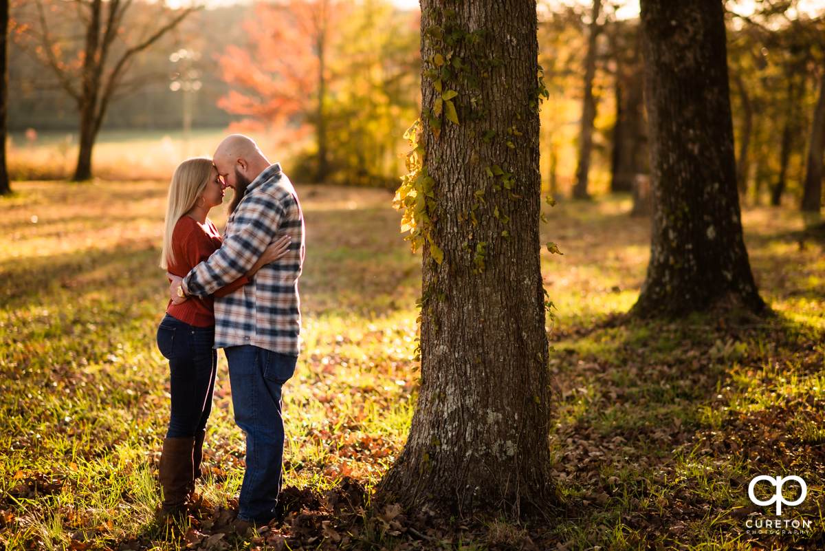 Engaged couple leaning in to each other near a tree in front of fall leaves at Famoda Farm.