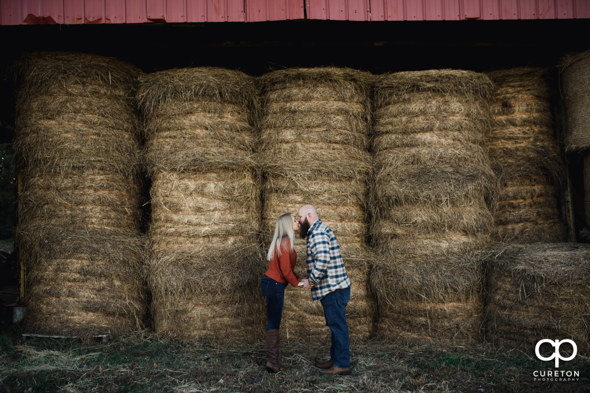Couple kissing in front of some hay bails.