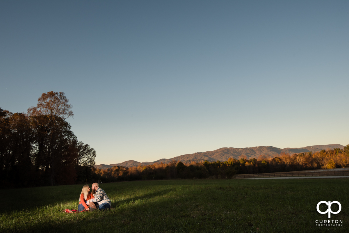 Future bride and groom sitting on a blanket in a field in front of a mountain backdrop during their engagement session at Famoda Farm.