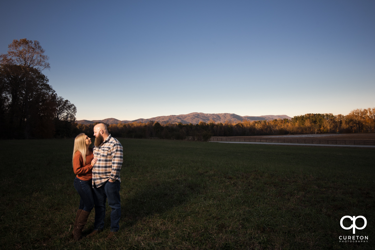 Future bride and groom in front of a mountain view during their engagement session at Famoda Farm.