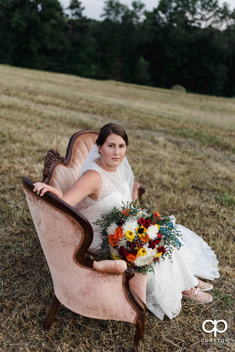 Bride sitting on a victorian couch in a field at Famoda Farms in Taylors SC.