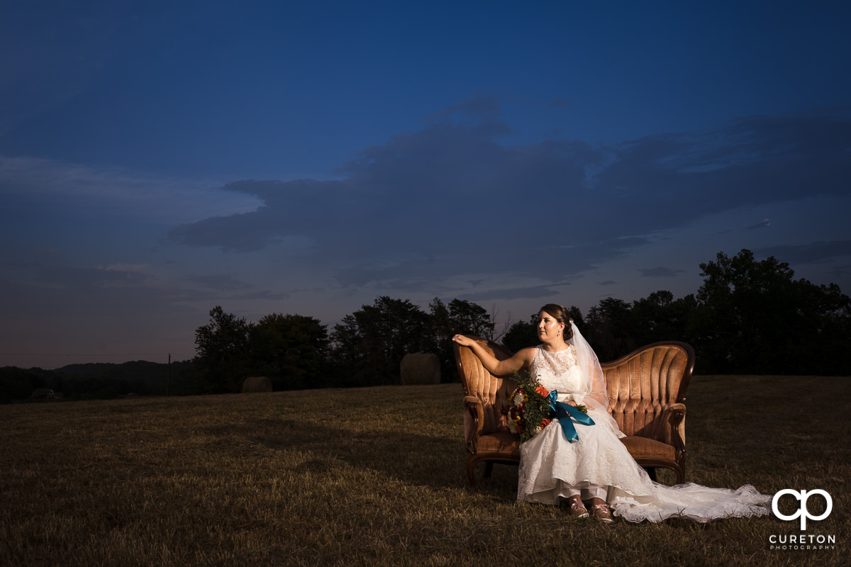 Bride sitting on a Victorian couch in a field at sunset during a pre wedding bridal session at Famoda Farms in Taylors,SC.