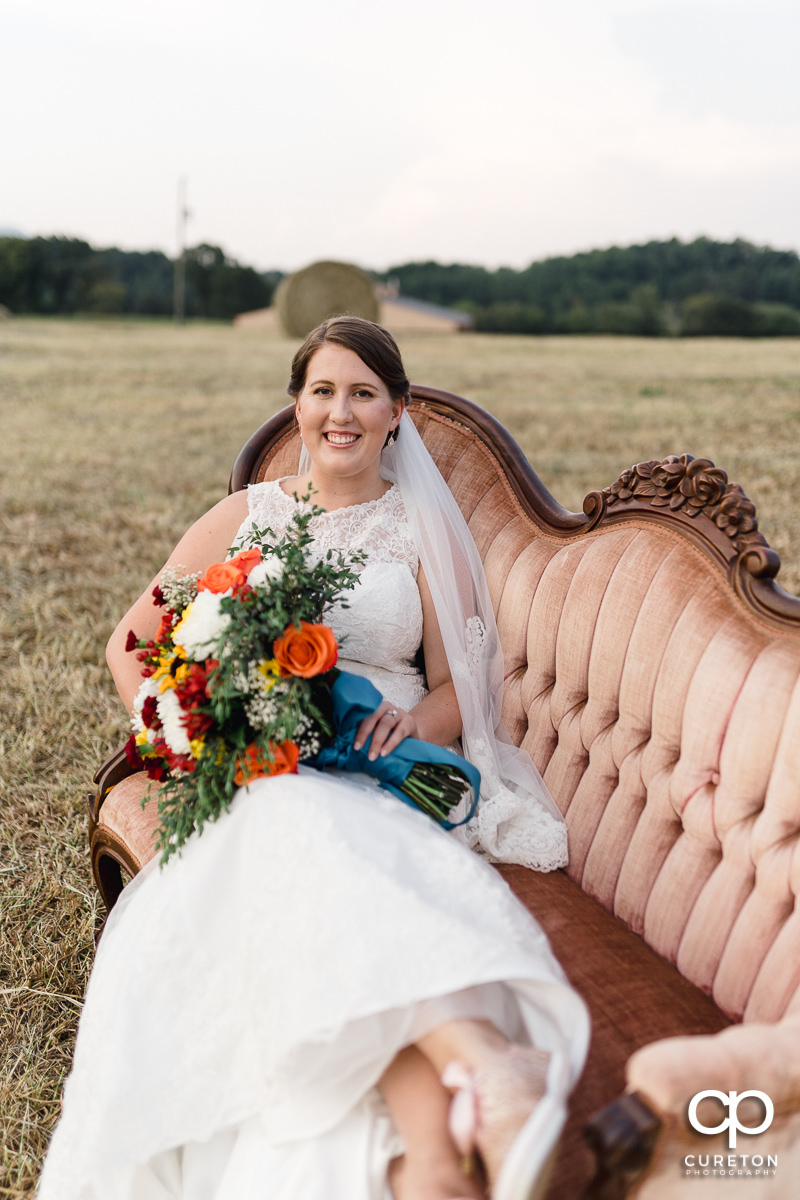 Bride sitting on a vintage couch in a field during a pre wedding bridal session at Famoda Farms in Taylors,SC.