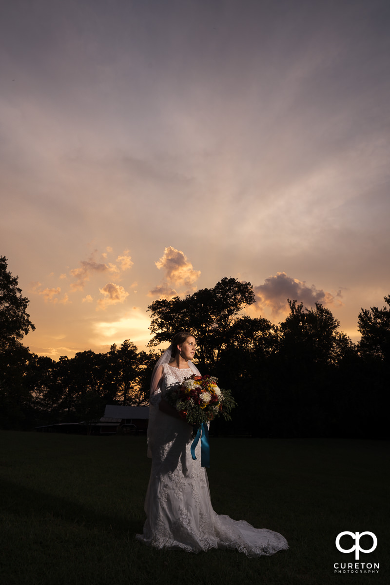 Bride standing in front of Famoda Farms at sunset.