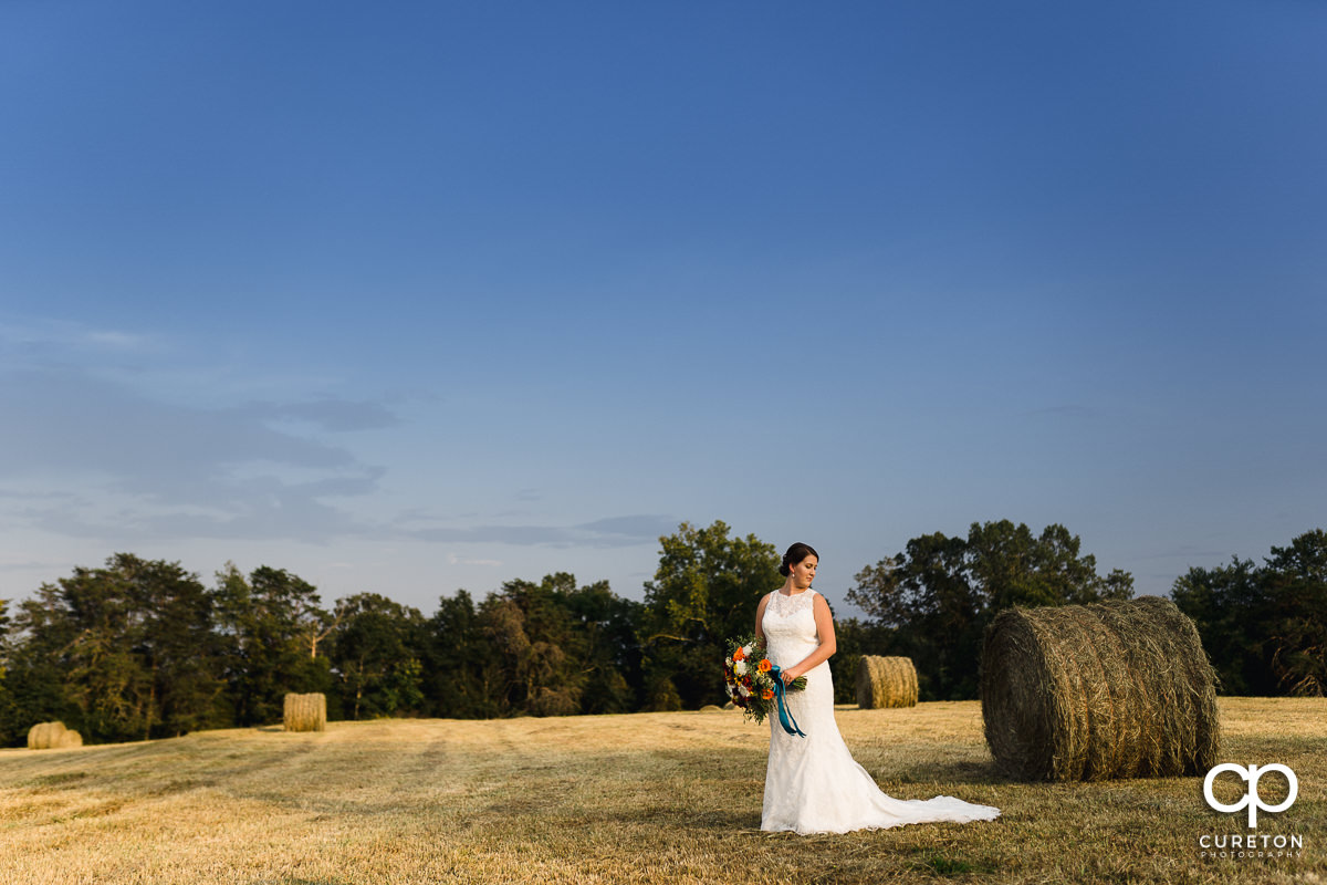 Bride next to some hay bales at Famoda Farms.