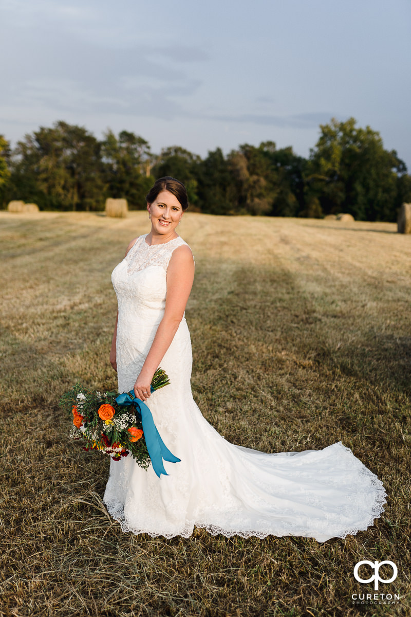 Bride smiling in a hay field.