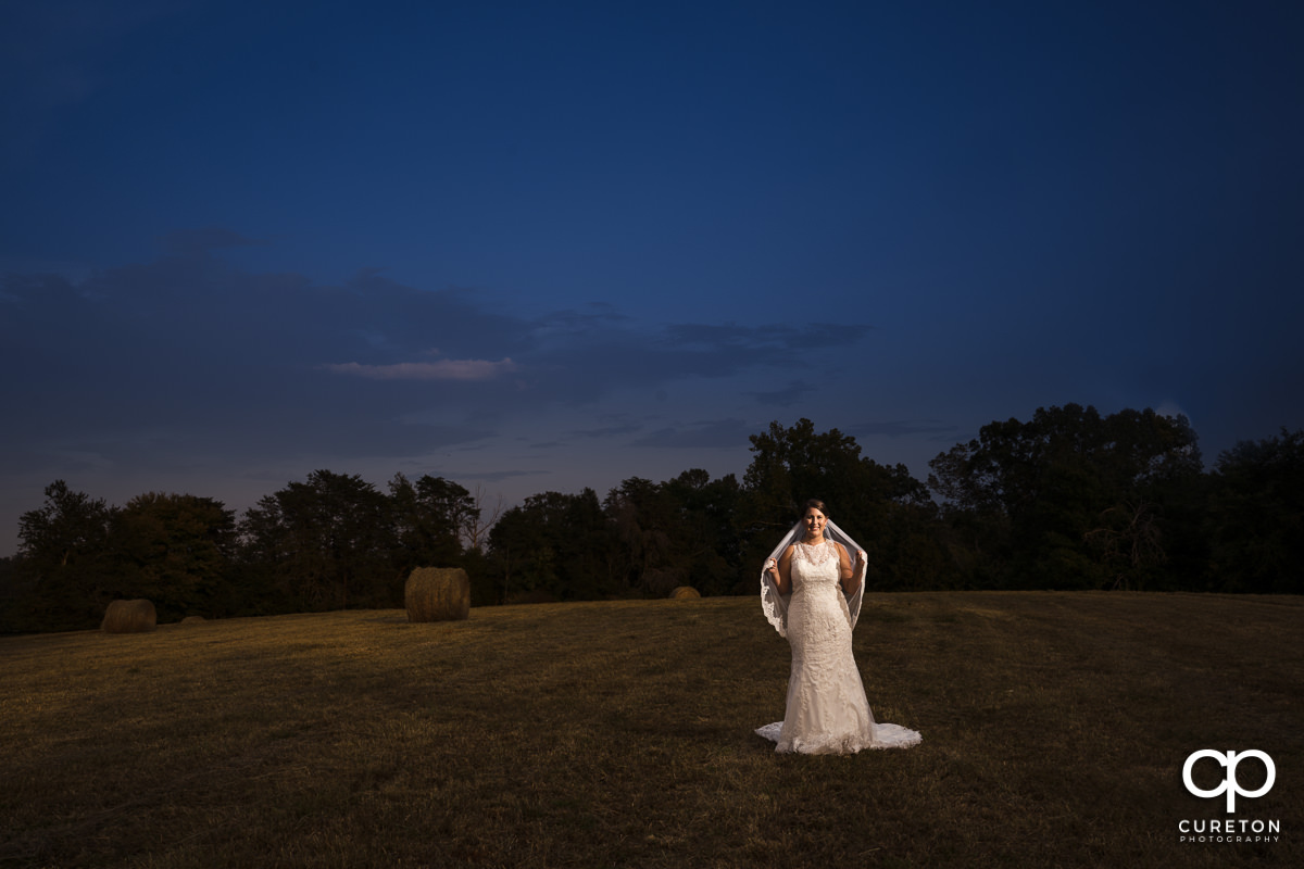 Bride holding her veil in a field at sunset during a pre wedding bridal session at Famoda Farms in Taylors,SC.
