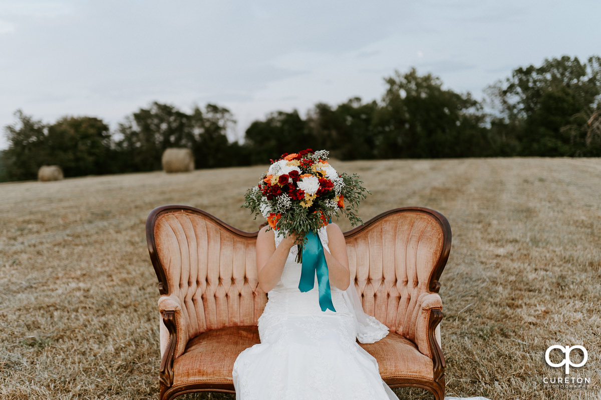 Bride holding her flowers in front of her face while sitting in a vintage vintage couch in a hay field.
