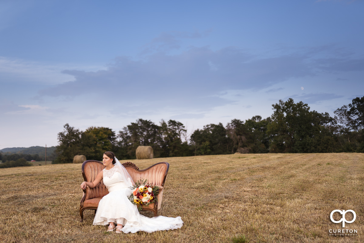 Bride on a couch in a field.