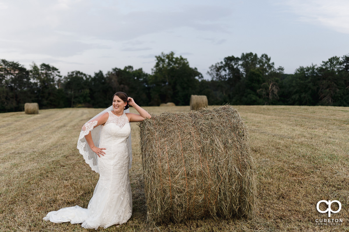 Bride laughing while leaning on a hay bale.