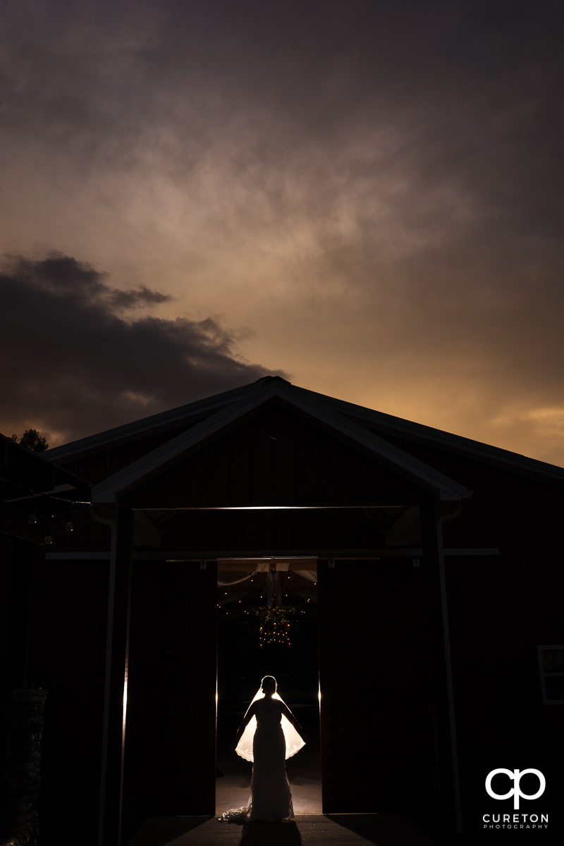 Bride backlit at sunset in a barn.