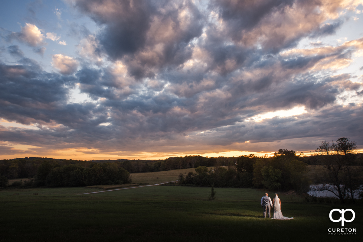 Bride and groom staring out into an epic sunset after their Famoda Farm wedding in Taylors,SC.