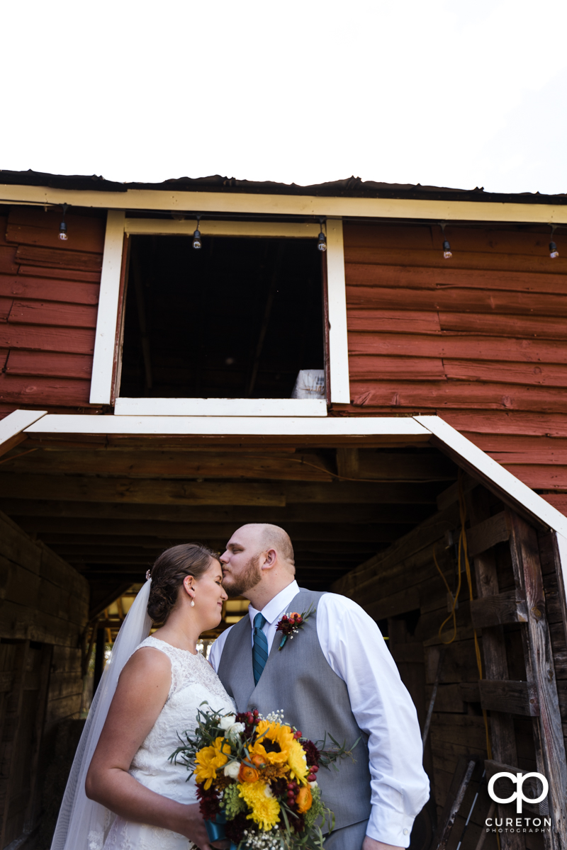 Groom kissing his bride on the forehead underneath a hay loft.