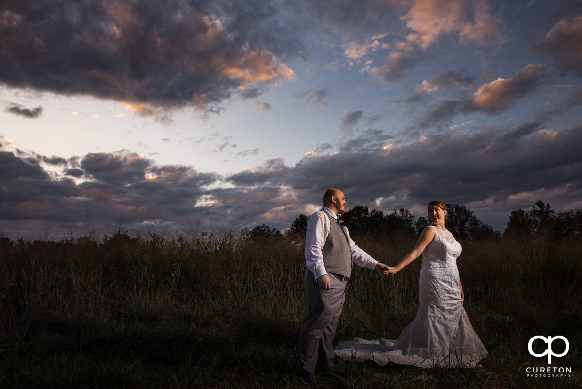 Bride leading her groom though a field of tall grass at sunset at their Famoda Farm wedding in Taylors,SC.