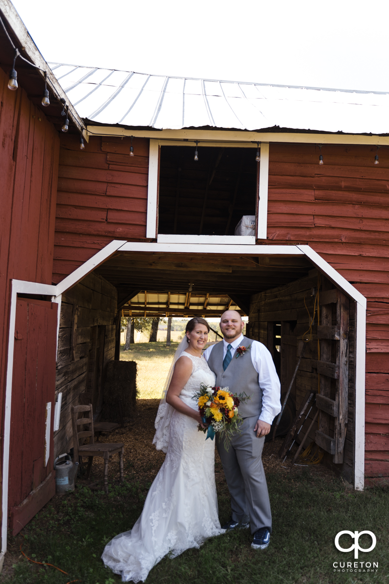 Bride and groom in front of a red barn in Taylors,SC.