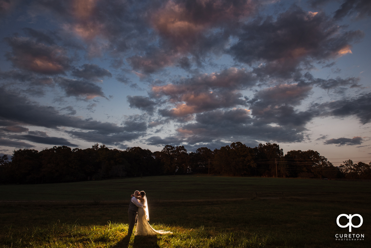 Bride and groom kissing underneath an epic sky at sunset at their wedding at Famoda Farm in Taylors,SC.