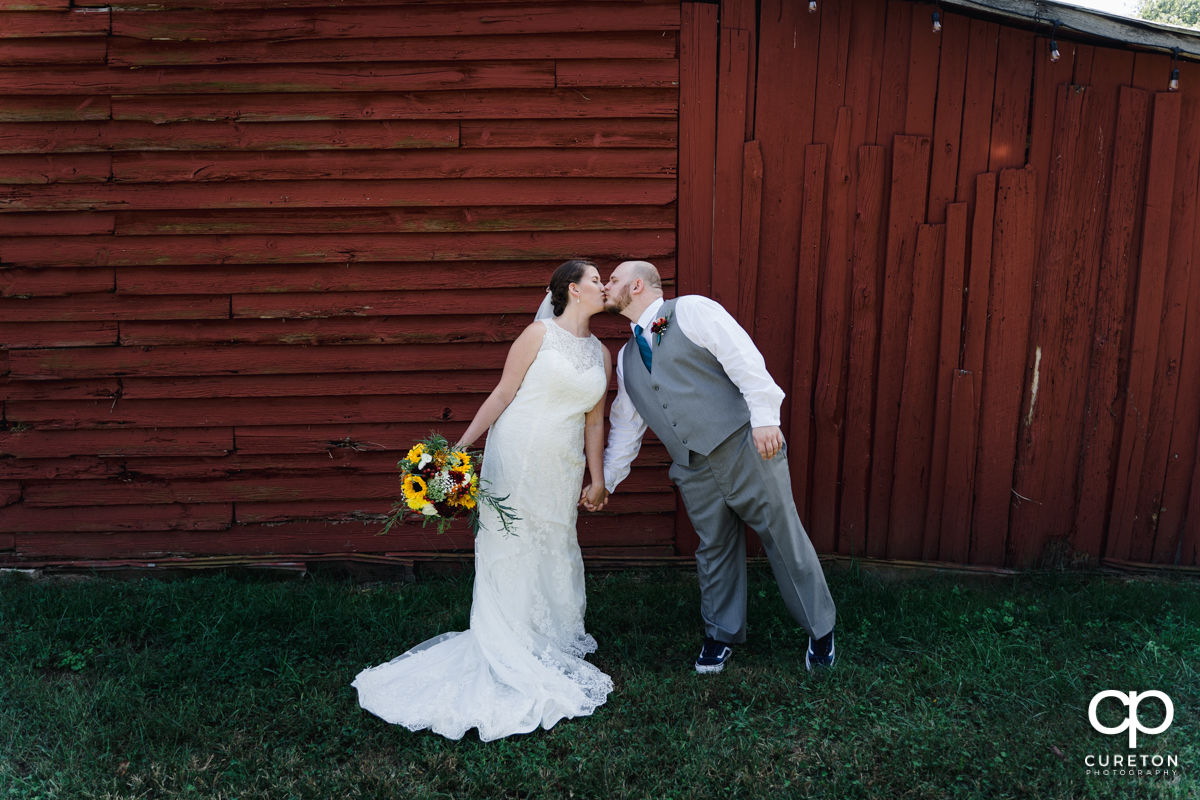Bride and groom kissing in front of a red barn.