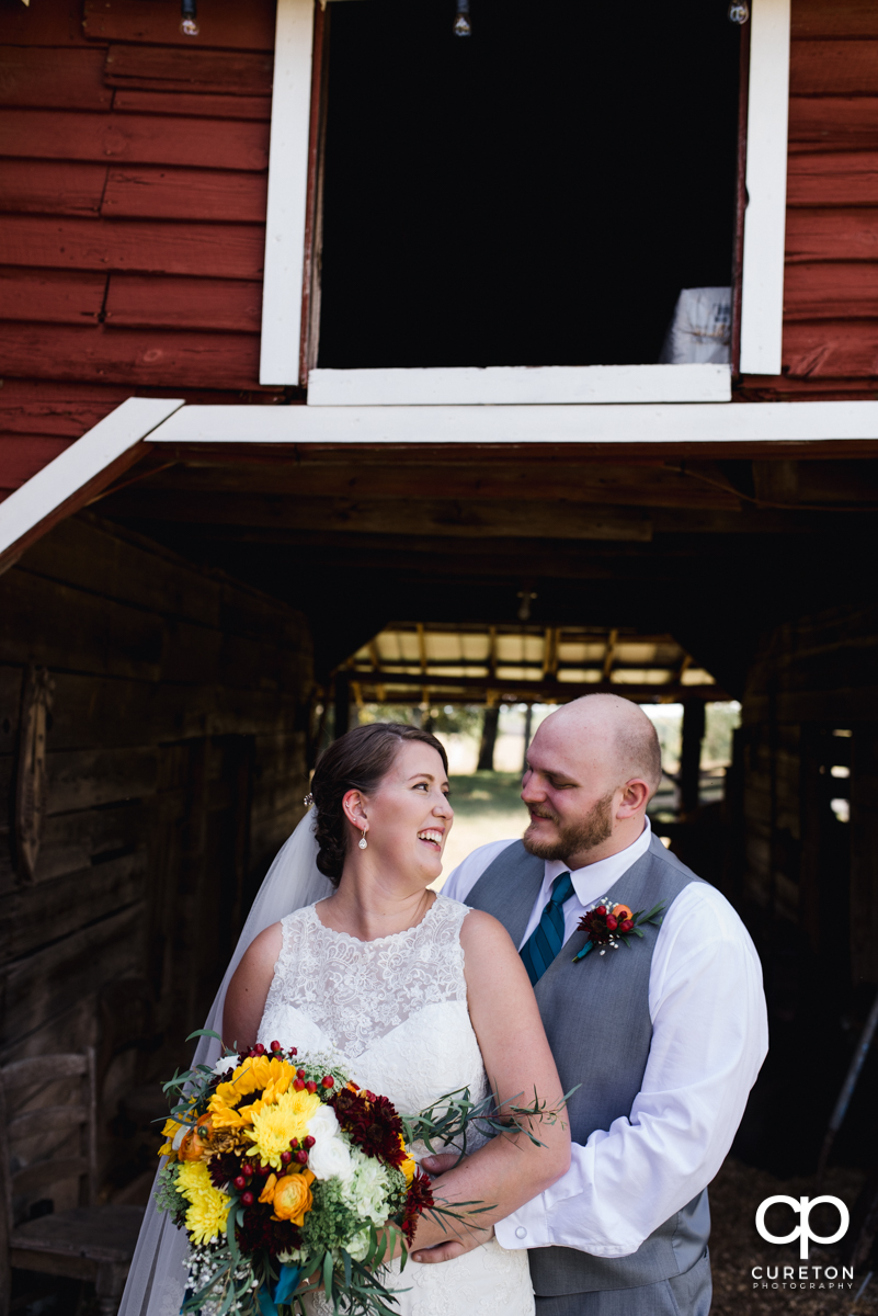 Groom smiling at his bride in front of a barn door.