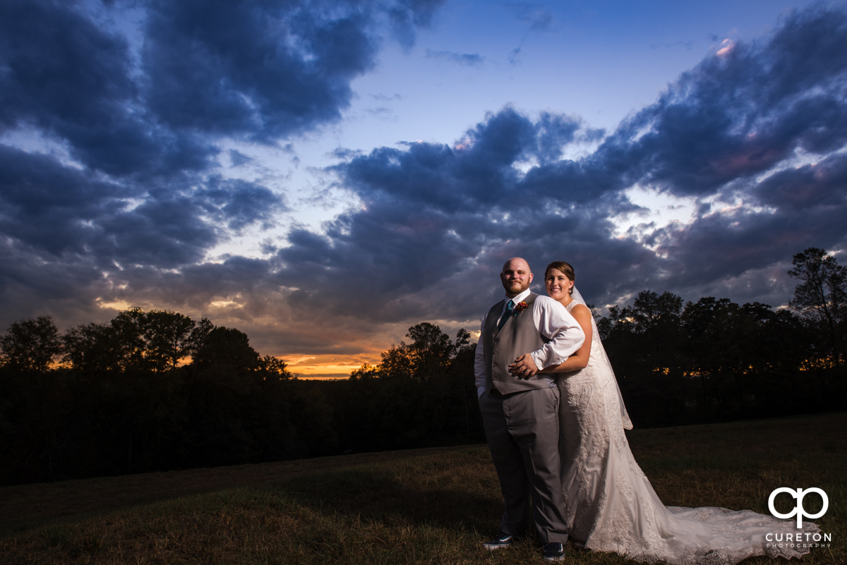 Bride and groom holding each other at sunset at their wedding at Famoda Farm.