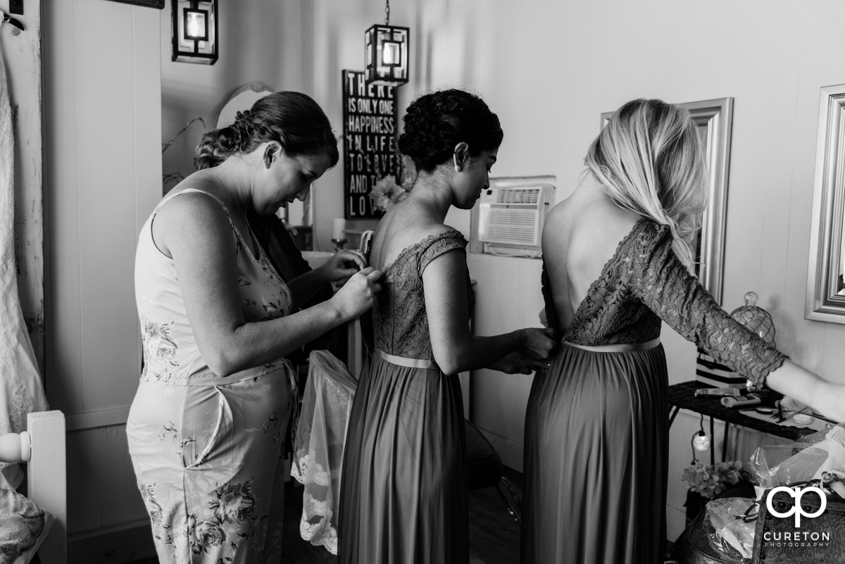 The bride helping her bridesmaids get dressed.