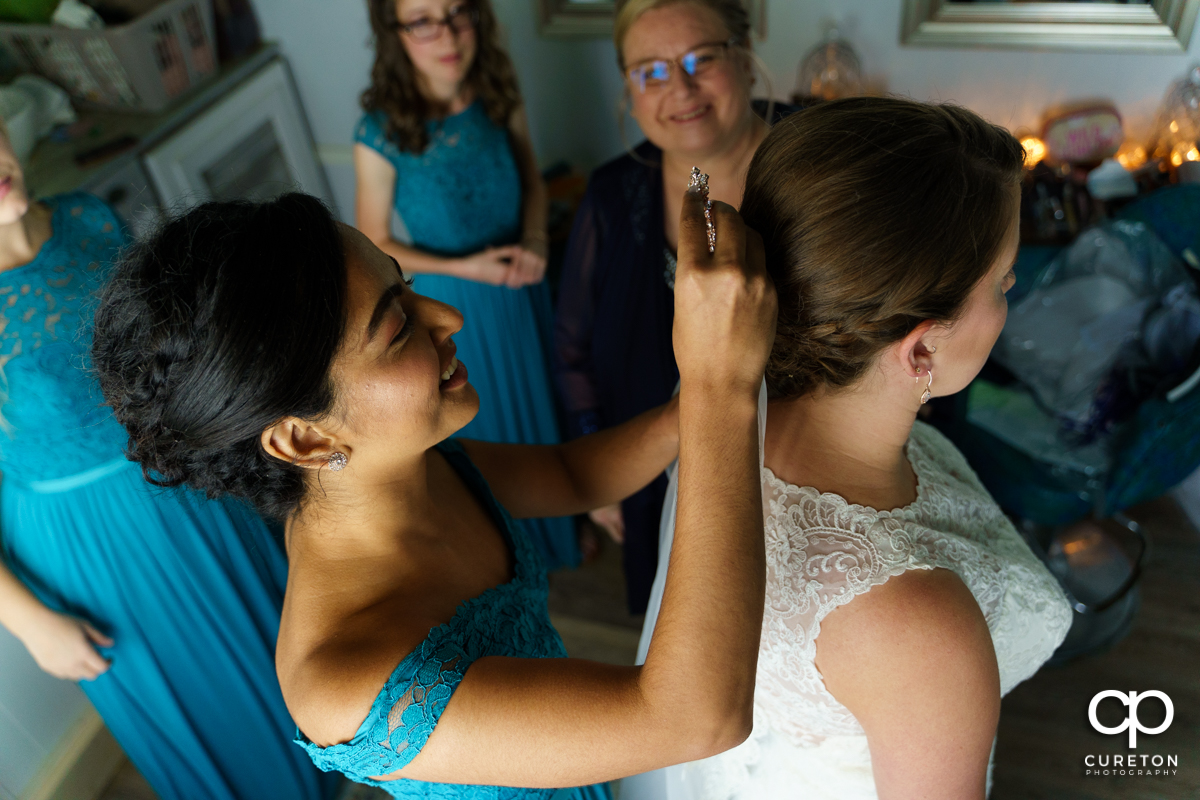 Bridesmaid putting in the bride's veil.