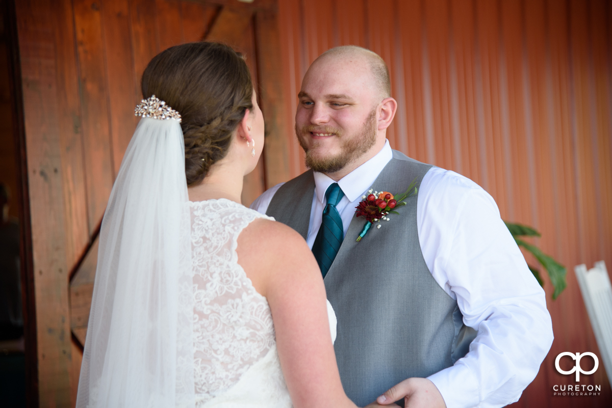 Groom smiling as he sees his bride in her dress for the first time on the wedding day.