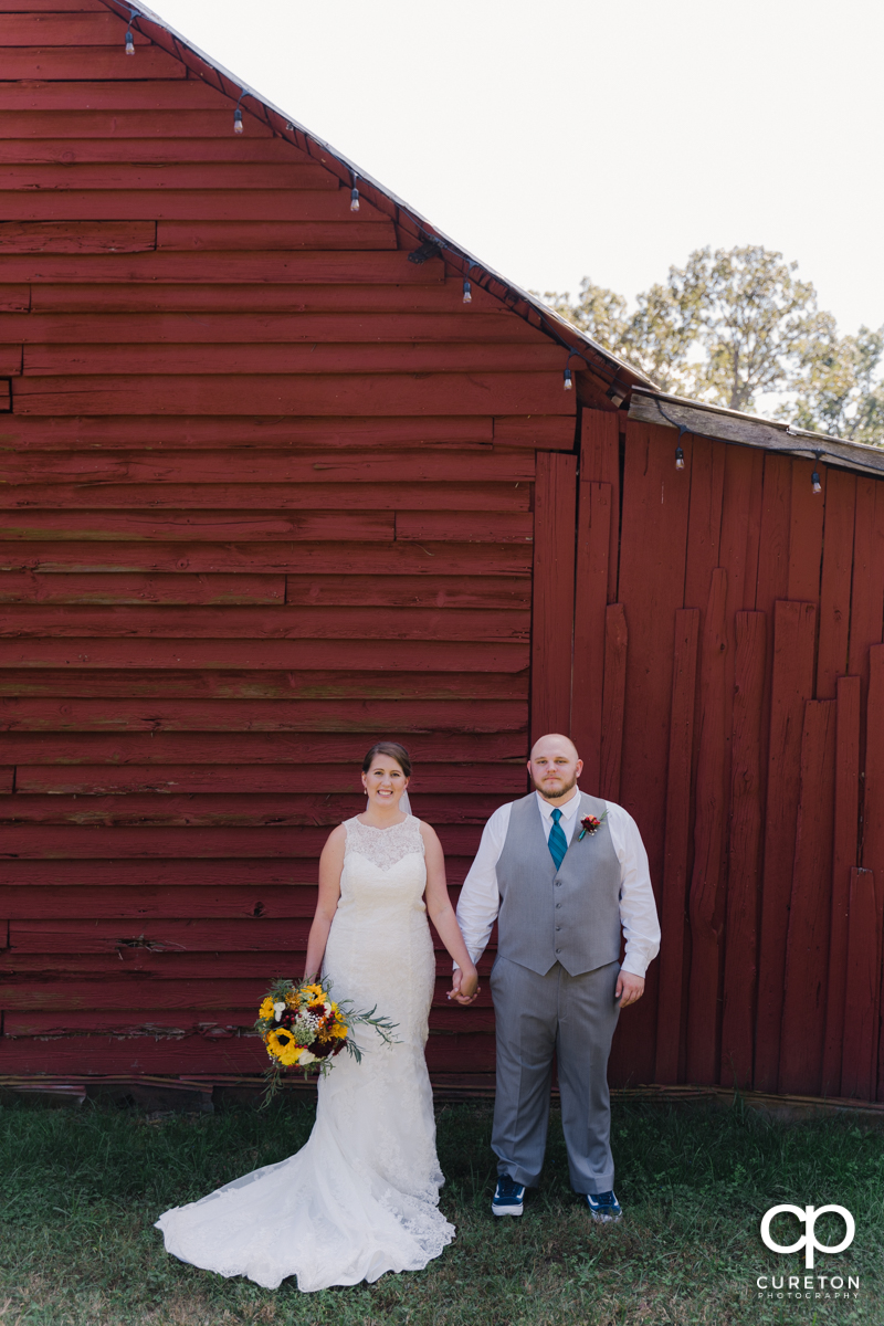 Bride and groom holding hands in front of a red barn.