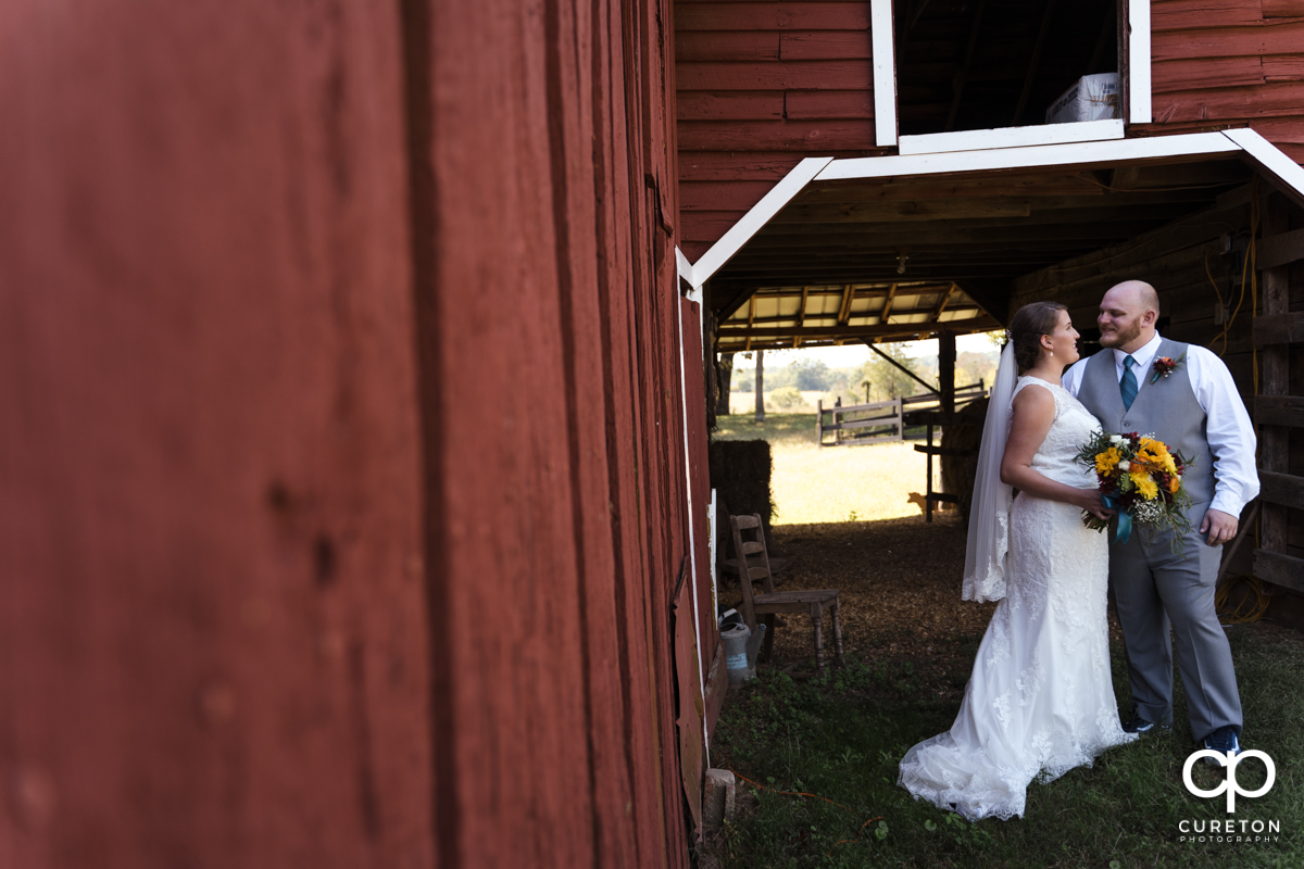 Bride and groom sharing a moment in front of the barn at Famoda Farms.