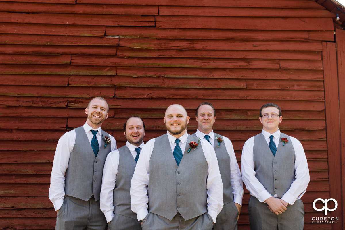 Groom and groomsmen in front of a red barn.